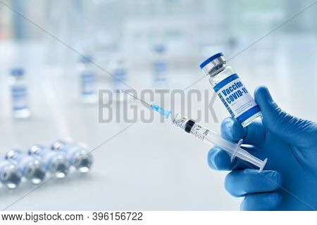 Male Doctor Hand Wears Medical Glove Holding Syringe And Vial Bottle With Covid 19 Corona Virus Vacc