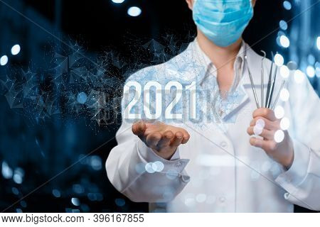 Doctor Dentist Shows The Numbers 2021 On A Blurred Background.