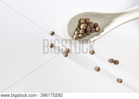 Black Peppercorns On White With Long Shadows. Black Peppercorns In A Spoon And A Bowl. Place For Tex