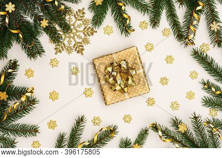 Festive Background With Gold Decoration , Green Spruce Branches And Shiny Golden Serpentine Confetti
