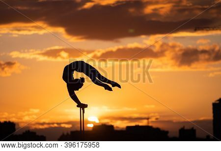 Flexible Female Circus Artis Keep Balance And Doing Contortion On The Rooftop Against Dramatic Sunse