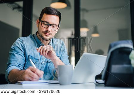 Close Up Portrait Of Handsome Man Working From Home Office Taking Reading And Writing Notes In Note