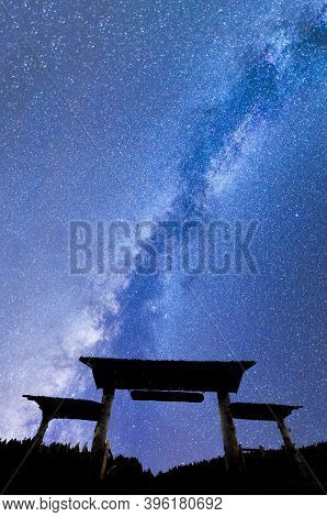 A View Of A Meteor Shower And The Milky Way With Wooden Entrance Door With A Roof And Fence Silhouet