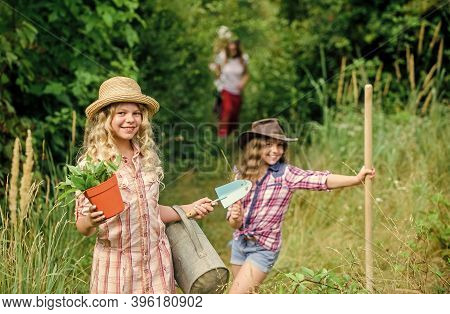 Sisters Helping At Farm. Eco Farming Concept. Adorable Girls In Hats Going Planting Plants. Kids Sib