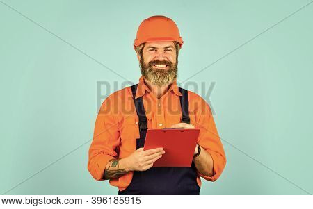 Manual Worker In Helmet. Worker With The Folder In Construction Uniform. Engineer Man With Sketches