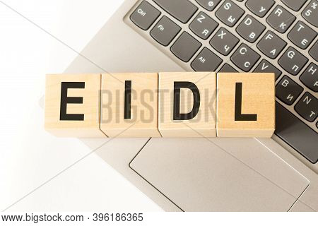 Word Eidl. Wooden Cubes With Letters Isolated On A Laptop Keyboard. Business Concept Image.