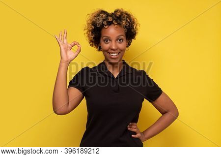 African American Woman Isolated On Yellow Background Cheerful And Confident Showing Ok Gesture.