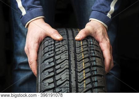 Closeup Of Mechanic Hands Holding A Tire On Dark Background. Replacement Of Winter And Summer Tires.
