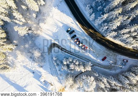 Winter Road In Mountains Aerial Drone View. Cars Parked Along Road In Mountains. Winter Aerial Backg