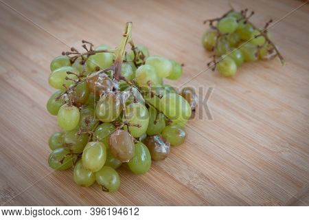 Unhealthy Green Portion Of Wilted Grape Fruits On A Table.