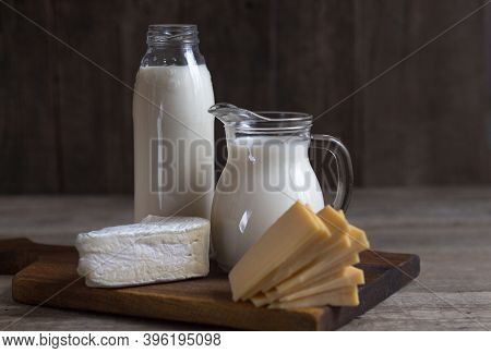 Delicious Fresh Milk On An Old Wooden Background. A Jug Of Milk And A Bottle Of Milk. Cheese. Copy S
