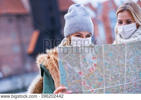 Two women wearing masks and holding map while sightseeing Gdank in Poland