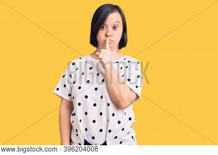 Brunette woman with down syndrome wearing casual clothes asking to be quiet with finger on lips. silence and secret concept.