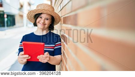 Beautiful brunette woman with down syndrome at the town on a sunny day using touchpad device leaning on a bricks wall