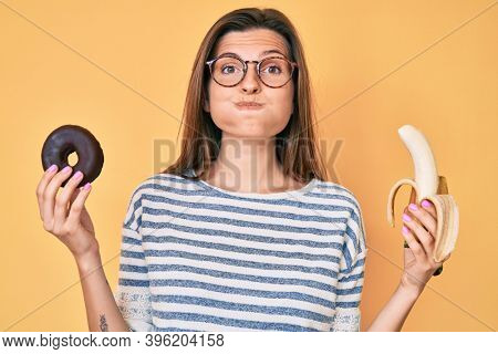 Beautiful caucasian woman holding banana and chocolate doughnut puffing cheeks with funny face. mouth inflated with air, catching air.