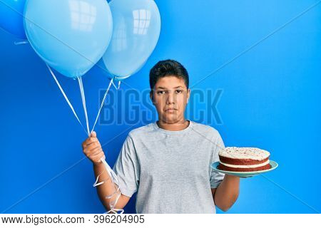 Hispanic teenager boy celebrating birthday with cake holding balloons puffing cheeks with funny face. mouth inflated with air, catching air.