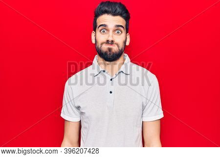 Young handsome man with beard wearing casual polo puffing cheeks with funny face. mouth inflated with air, crazy expression.