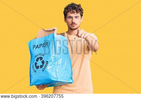 Young handsome man with curly hair holding recycling wastebasket with paper and cardboard pointing with finger to the camera and to you, confident gesture looking serious