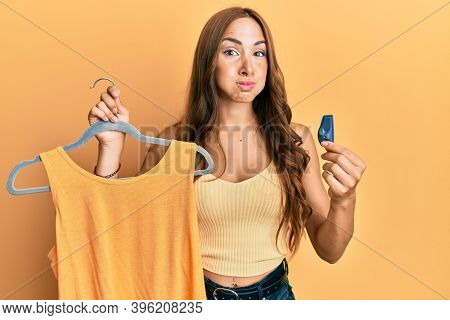 Young brunette shopkeeper woman holding clothes and security alarm puffing cheeks with funny face. mouth inflated with air, catching air.
