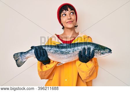 Beautiful brunettte fisher woman wearing raincoat holding fresh salmon smiling looking to the side and staring away thinking.