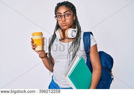 Young african american woman with braids wearing student backpack drinking coffee puffing cheeks with funny face. mouth inflated with air, catching air.