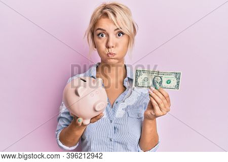 Young blonde girl holding dollar and piggy bank puffing cheeks with funny face. mouth inflated with air, catching air.