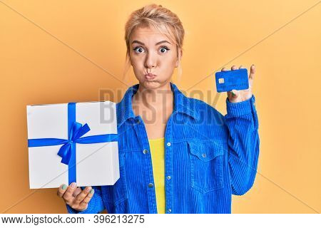 Young blonde girl holding gift and credit card puffing cheeks with funny face. mouth inflated with air, catching air.
