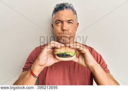 Handsome middle age mature man eating a tasty classic burger puffing cheeks with funny face. mouth inflated with air, catching air.