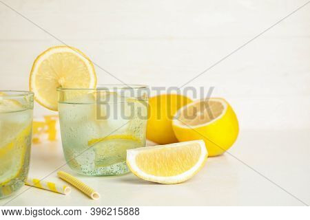 Soda Water With Lemon Slices And Ice Cubes On White Table. Space For Text