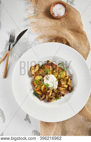 Fried potato with mushrooms and sour cream. Sackcloth and wooden kitchenware on rustic table. Top view