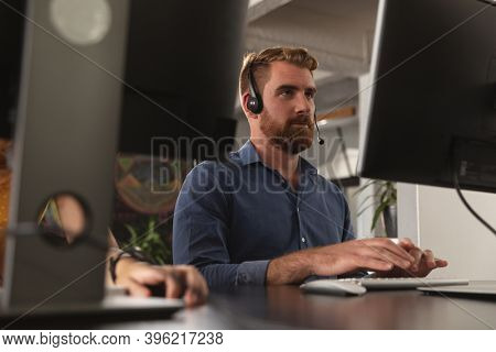 Close up of a young Caucasian man sitting at a desk using a computer and wearing a phone headset in a office, between computer screens, with the hand of a colleague working beside him on the desk