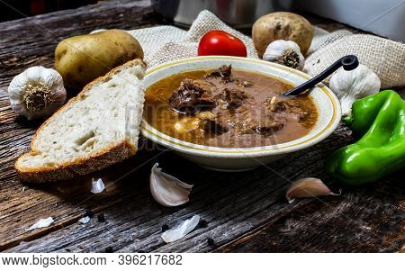 Traditional Slovak beef stew on rustic wooden table with ingredience