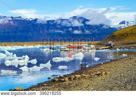 ICELAND, SCAFTAFETL PARK, ICE LAGOON JOKULSAURLOUN - July 10, 2014: The icebergs and ice floes. Picturesque yellow boat for a sightseeing tour. The concept of northern and photo tourism