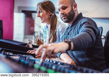 Singer or artist and sound engineer working in the studio at a production