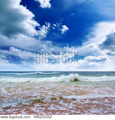 Bright seascape with white clouds, blue sky and beautiful sea surf.
