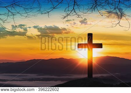 Silhouette Of Cross On Mountain With Sunset Background.