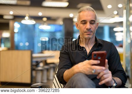 Portrait Of Man Sitting In Coffee Shop Using Mobile Phone