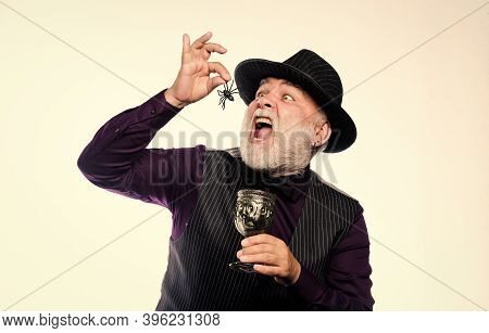 Happy Haunting. Halloween Holiday Costume. Mature Man Magician In Witch Hat. Evil Wizard Cooking Mag