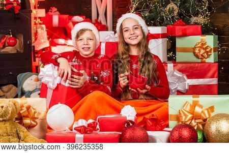 Children Little Happy Girl And Boy Find Gifts Near Christmas Tree. Merry Christmas. Discover Beauty