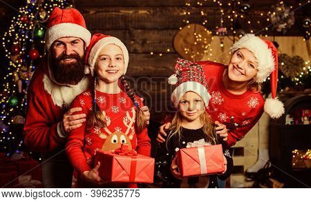 Parents And Children Opening Christmas Gifts. Christmas Tradition. Boxing Day. Happy Holidays. Fathe