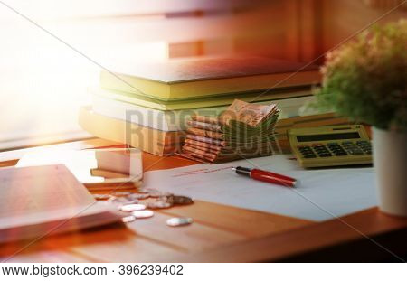Banknotes And Books On Wooden Table With Blurred Coins And Paperwork For School Scholarship Applicat