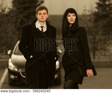 Young fashion business couple on city street Stylish man and woman in classic black coats