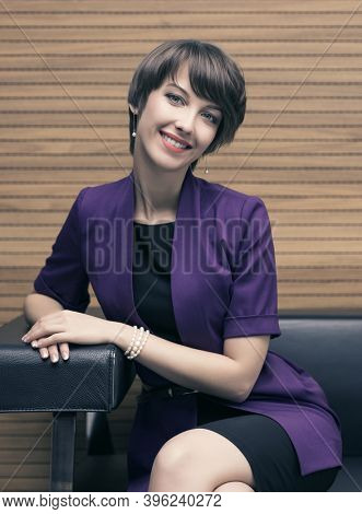 Young fashion business woman sitting on couch in office interior Stylish female model with pixie hair style in purple blazer and black pencil skirt