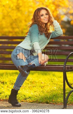 Happy young woman sitting on bench Stylish fashion model in ripped jeans and light blue pullover