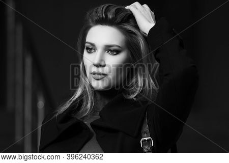 Young fashion blonde business woman walking on city street Stylish female model in classic black coat