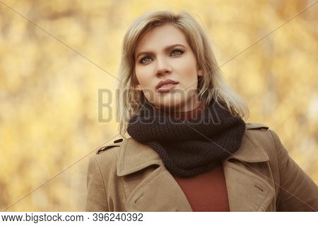 Happy young blonde fashion woman walking in autumn park Stylish female model in classic beige coat and black scarf