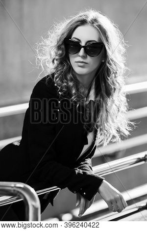 Young fashion blonde business woman leaning on railing Stylish female model in black jacket and sunglasses