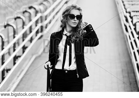 Young business woman in sunglasses with handbag walking on city street Fashion female model in black jacket and jeans