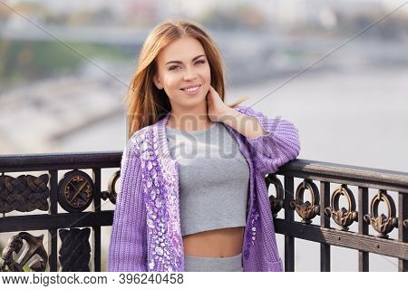 Happy young woman leaning on the railing Stylish fashion model in light purple cardigan and gray t-shirt