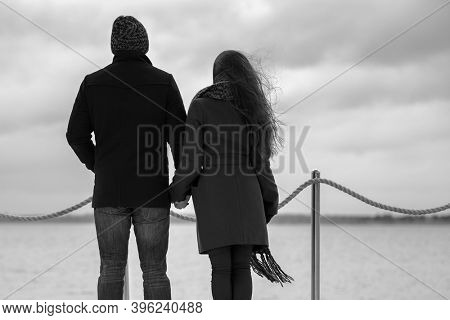 Happy young fashion couple in love walking outdoor Stylish man and woman in classic coats beanie and scarf